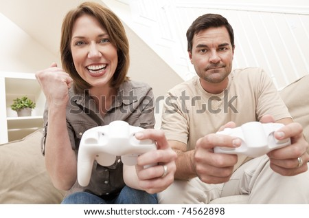 Man and woman married couple having fun playing computer console game together, the woman is celebrating winning the man is upset losing