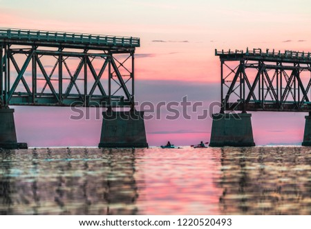 Man and woman married coupled in kayaks kayaking through the broken bridge at sunset near Key West in the Florida Keys in the Atlantic Ocean