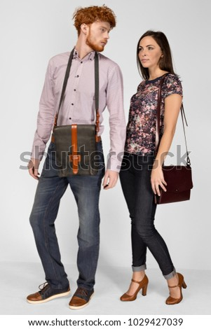 Man and woman model in the studio advertise leather bags. They are dressed in casual clothes jeans, shirts, shoes. Isolated background. stock photo