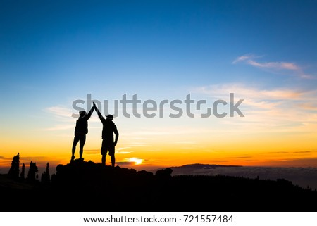 Man and woman on rocky mountain looking at beautiful sunset inspirational landscape view Tenerife Canary Islands.
