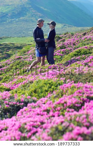 Man and woman on vacation in the mountains. Couple in love among the flowers. Bushes blooming pink rhododendron. Carpathian mountains, Ukraine