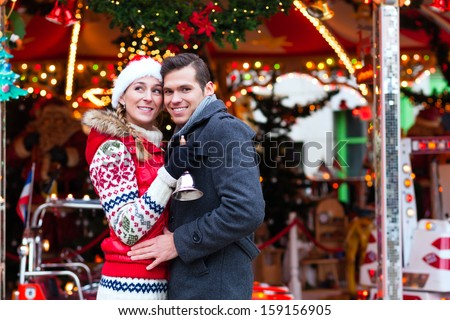 "Man and woman or  a couple  or friends during advent season or holiday in front of a carousel or ""marry-go-round"" on the Christmas or Xmas market"