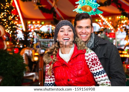 Man and woman or  a couple  or friends during advent season or holiday in front of a carousel or merry-go-round on the Christmas or Xmas market