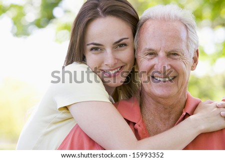 Man and woman outdoors embracing and smiling - stock photo