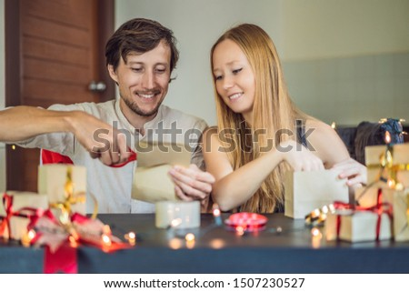 Man and woman packing presents. Present wrapped in craft paper with a red and gold ribbon for christmas, birthday, mother's day or valentine