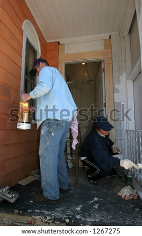 man and woman painting exterior  of house