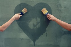 Man and woman painting heart on the concrete wall