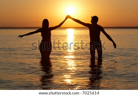 man and woman pair in water on sunset background
