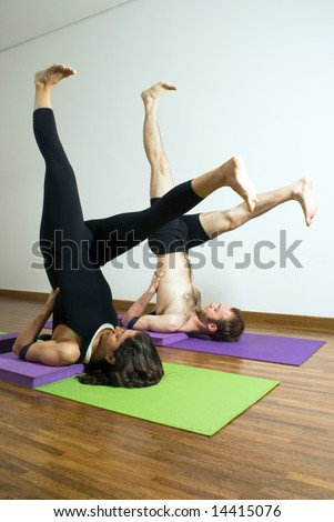 Man and woman performing yoga together on mats. Lying on shoulders, feet in air above head, legs spread. Vertically framed shot.