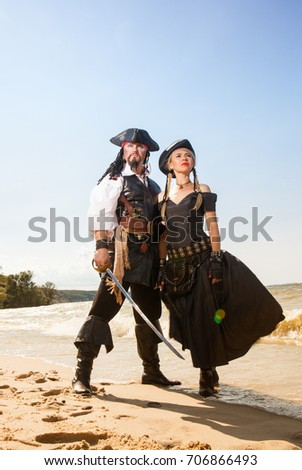 Man and woman pirates on the beach