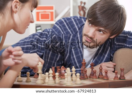 man and woman playing chess at home