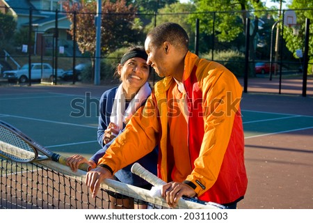 Man and woman playing tennis smiling at each other as they stand at the net. They are holding rackets. Horizontally framed photo.