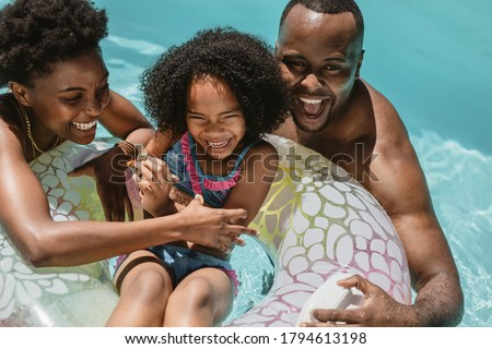 Man and woman playing with their daughter on inflatable ring in swimming pool. Family of three enjoying summer holidays in swimming pool.