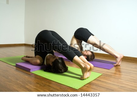 Man and woman practicing yoga in a studio - Horizontally framed photograph