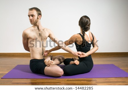Man and woman practicing yoga with their arms entwined on a purple yoga mat. Horizontally framed photograph