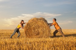 Man and woman pushing towards each other a straw bale. Concept of the dialectical principle of The Unity and The Struggle of Opposites