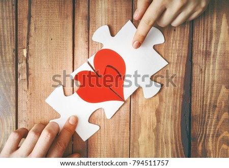 Man and woman put the red heart puzzle together. Concept of Valentine's day.