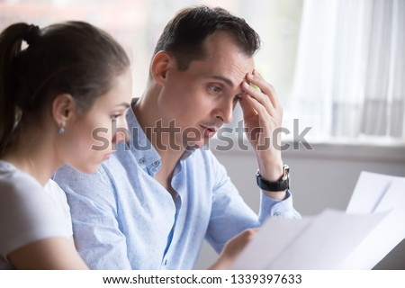 Man and woman reading contract for real estate property purchase. Employer and employee, customer and client, boss and worker, teacher and student, husband and wife studying contract. People at work