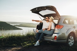 Man and Woman Relaxing Inside Car Trunk Enjoying Weekend Road Trip, Travel and Adventure Concept