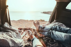 Man and woman relaxing inside trunk and watching at the sea. Fall car trip in sunset. Freedom travel concept. Autumn weekend.