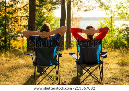 man and woman resting on the lake