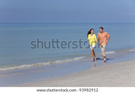 Man and woman romantic couple running holding hands on a deserted tropical beach with bright clear blue sky