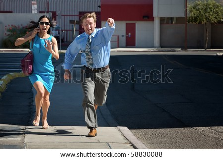 Man and woman run down street to catch taxi. - stock photo