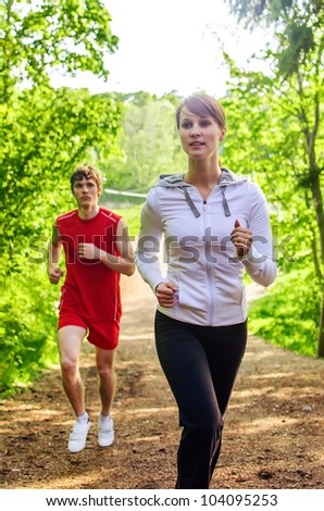 Man and woman running along the forest path