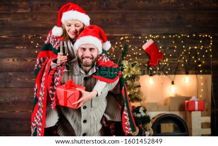 Man and woman santa claus hats cheerful celebrating new year. Merry christmas. Guy piggybacking girl. Celebrating together. Celebrating winter holiday. Christmas fun. Interesting ideas celebration.