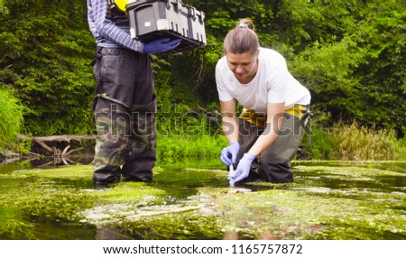 Man and woman scientist environmentalist standing in a river. Woman taking sample of water. Man holding toolbox Stock foto ©