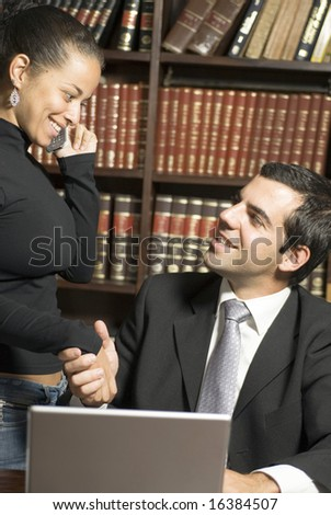 Man and woman shake hands over laptop. They are smiling at each other while she is on the cellphone. Vertically framed photo.