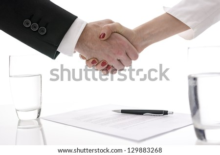 Man and woman shaking hands above table with signed contract.