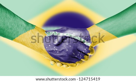 Man and woman shaking hands, arms wrapped in the flag of Brazil