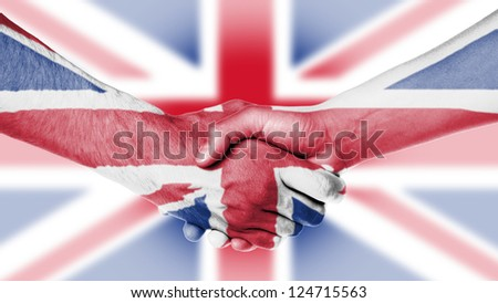 Man and woman shaking hands, arms wrapped in the flag the UK