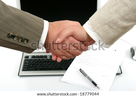 man and woman shaking hands in front of computer and document with pen