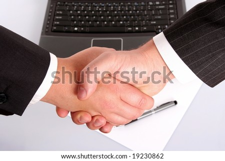 man and woman shaking hands in front of laptop and white paper with pen