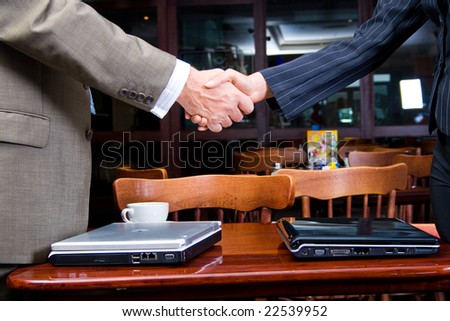 man and woman shaking hands over two laptop