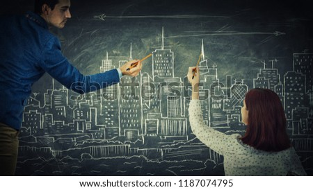 Man and woman sharing thoughts together drawing a city on a blackboard. Urbanistic planning, people idea exchange, business partnership and teamwork innovation concept.