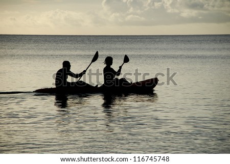 Man and woman silhouetted at sea in a kayak - stock photo