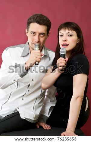 Man and Woman Singing Karaoke on red burgundy background