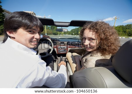 Man and woman sitting in a convertible look back