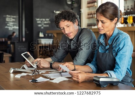 Man and woman sitting in cafeteria discussing finance for the month. Stressed couple looking at bills sitting in restaurant wearing apron. Café staff sitting together looking at expenses and bills.