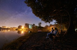 Man and woman sitting on bench on the shore near lake under tree. Couple enjoying view of night sky full of stars, Milky way, quiet water surface, city lights on background. Outdoor lifestyle concept