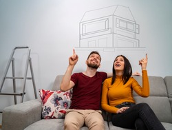 Man and woman sitting on sofa dreaming about new home, dreams come true