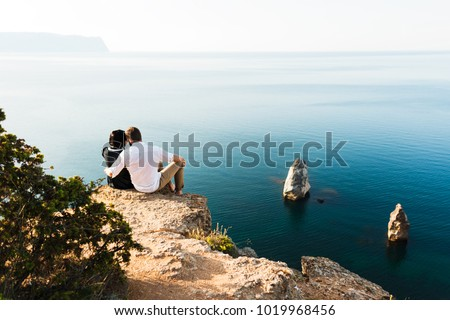 Man and woman sitting on the edge of a cliff by the sea. Honeymoon. Honeymoon trip. Man and woman at the sea. Man and woman traveling. Couple hugs. Couple kissing. Newly married couple. Lovers