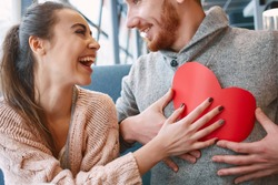 man and woman smiling and holding a large paper heart. Two people in cafe communicate, laughing and enjoying the time spending with each other. Couple in love on a date.  Valentines Day concept