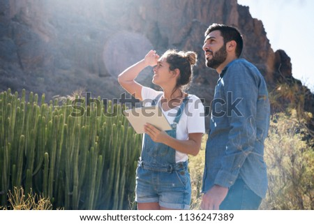 Man and woman stand and look at the horizon, they are surrounded by mountains and cactus