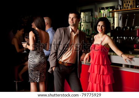 man and woman standing beside nightclub bar smiling