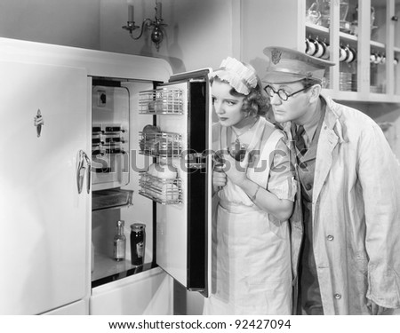 Man and woman standing in front of a refrigerator