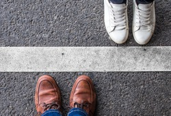 Man and woman standing opposite of each other, divided by a white line. Social distancing, quarantine, borders and barrier concept.